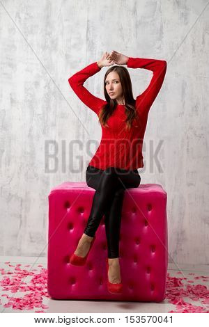 Fashion studio shoot of posing woman in red sweater on big pink cube