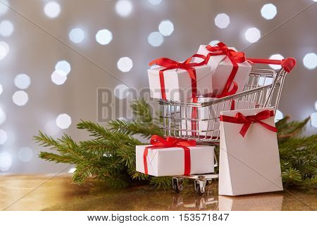 Shopping trolley with gift boxes and brenches of fir-tree with decoration on a grey background with light of garland. Christmas and New Year sale.