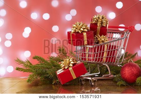 Shopping trolley with gift boxes and brenches of fir-tree with decoration on a red background with light of garland. Christmas and New Year sale.