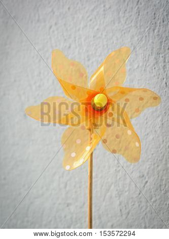 Yellow pinwheel against the background of a gray wall