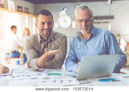 Beautiful businessmen in classic shirts is using a laptop talking and smiling while working in office