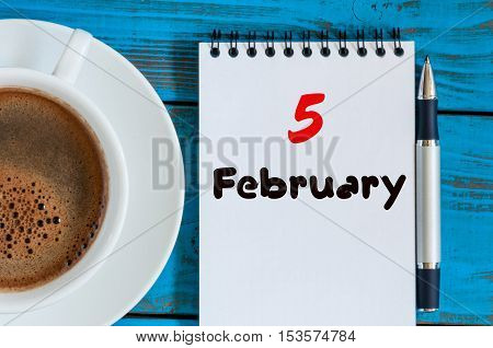 February 5th. Day 5 of month, calendar in notepad on wooden background near morning cup with coffee. Winter time. Empty space for text.