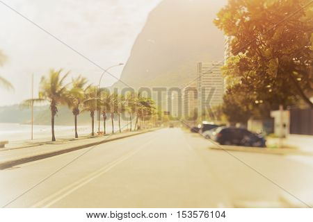 Tilt shift shooting of road in Rio de Janeiro on a sunny summer day palms residential houses far mountains and beach