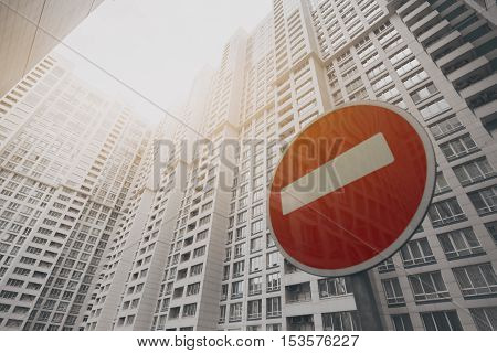 Contemporary white and grey skyscraper apartment building in Moscow on a sunny day with a red stop road sign reflecting the building view from bottom