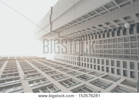 White and grey contemporary residential skyscraper apartment building in Moscow on a cloudy day two housing body regular windows view from bottom