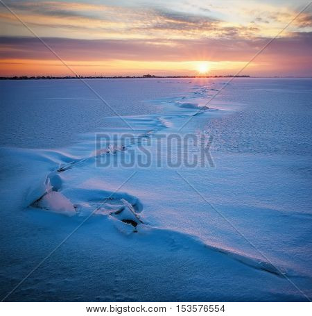 Winter landscape with frozen lake cracks and sunset sky.