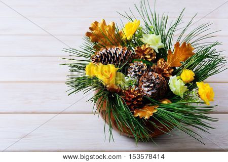 Christmas table decoration with pine branches and golden cones. Christmas centerpiece with golden decor. Christmas party background. Copy space.