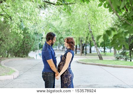 Happy pregnant woman with husband standing together in foliage. Pregnancy in long dress. Future daddy in jeans and blue shirt.