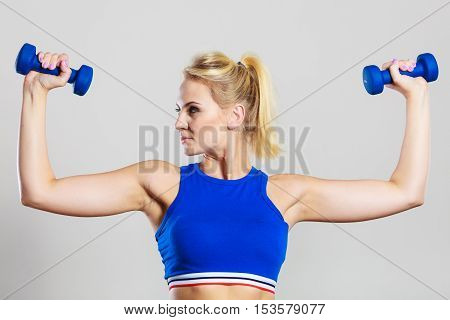 Sporty woman lifting light dumbbells weights. Fit girl exercising building muscles. Fitness and bodybuilding.