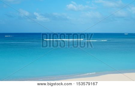 Sandy beach backdrop with waves and blue sky tropical holiday concept
