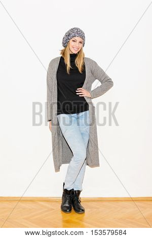 Portrait of beautiful young blonde modern woman in casual autumn outfit, standing by the white wall. Studio lighting, no retouch.
