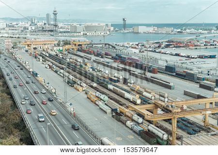 Barcelona harbor with lots of cargo colorful containers cranes cars and funicular in the back view from above