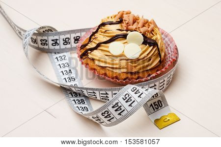 Appetite and gluttony concept. Fattening problem. Cake cupcake with measuring tape on table