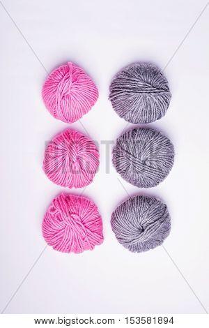 Six balls of cotton soft yarn shot from above on white background. Three gray and three pink soft wool yarns. Minimalist, studio lighting, no retouch, no filter.