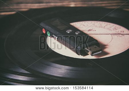 mp3 player on old vinyl record on the wooden table, selective focus and toned image