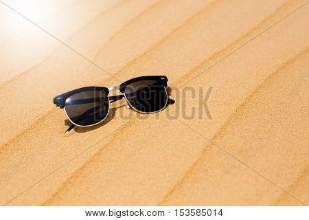 black Sunglasses on summer Desert sand dunes on the sand