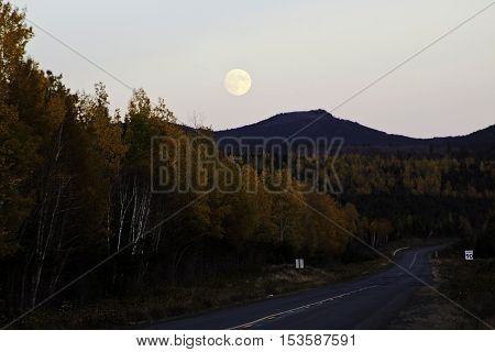 Full moon rising before sunset on Route 180 an old logging road though a line of autumn trees to a colorful scenery in the distance on a colorful day in October.
