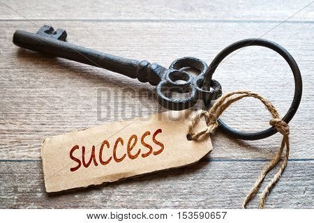 Keys to Success - Concept photo. Old key with paper label on wooden background - Success text.