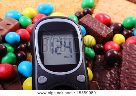 Glucose meter heap of candies cookies and brown cane sugar unhealthy food concept of diabetes and reduction eating sweets