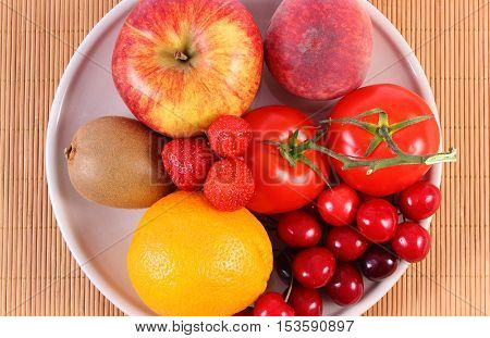 Fresh ripe fruits and vegetables lying on plate concept of healthy food nutrition and strengthening immunity