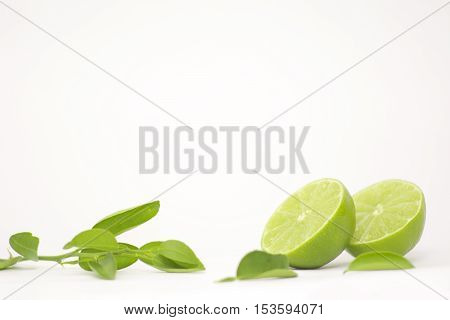 Fresh lemon sliceds with lemon tree leaves in a withe background.