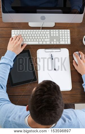 Man using computer on wooden table