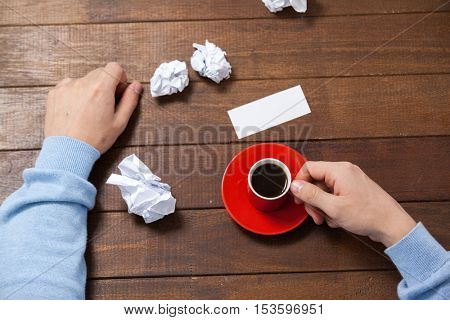 Man holding cup of coffee on wooden table