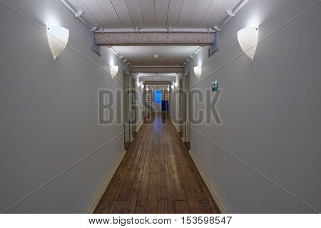 Long abstract white corridor of a wooden house with parquette floor