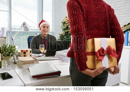 Business lady hiding present for chief behind her back