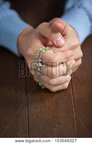 Praying hands of man with a rosary on wooden desk