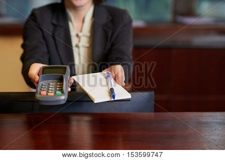 Cropped image of receptionist giving payment terminal and notepad to guest