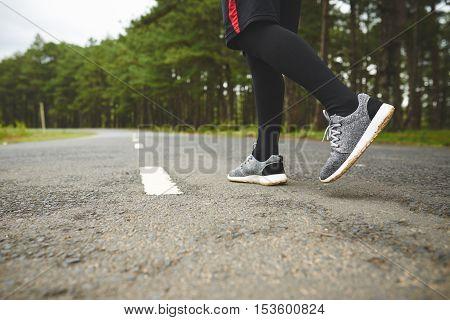 Feet of jogger ready to run along the road