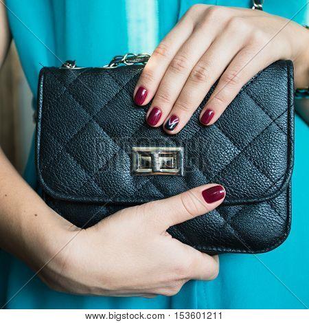 Female Nails With Red Nail Polish And A Beautiful Black Handbag