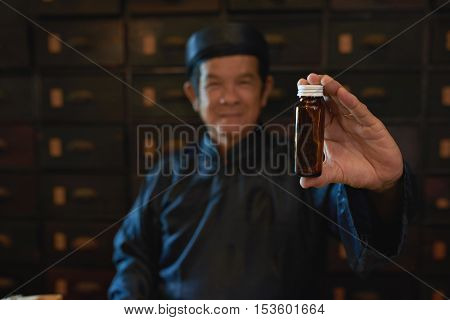 Traditional medicine practitioner showing empty glass bottle