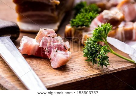 Raw smoked bacon slices on wooden board with cumin and herbs.