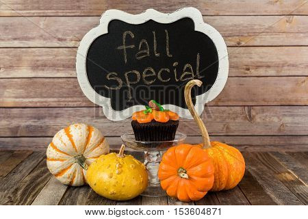 Fall pumpkin muffin with chalkboard sign and decorative gourds