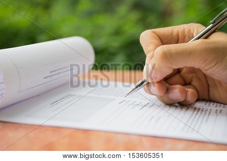 Hand with pen over application form, white paper