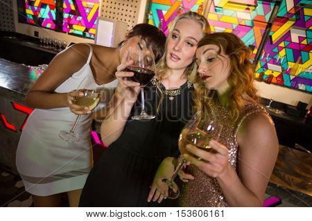 Three female friends having glass of champagne at bar