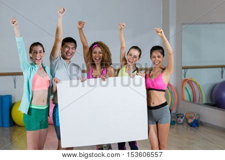 Portrait of group fitness team holding blank placard and clenching fists in fitness studio