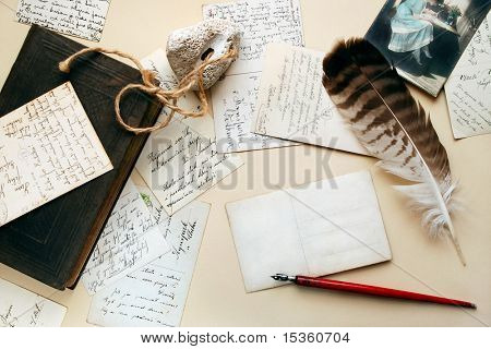 Vintage background as still-life with old postcards, pen, book, stone and feather