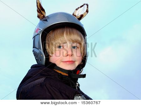 Smiling boy in a protective ski helmet with funny tiger ears