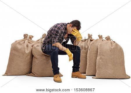 Depressed farmer sitting on a burlap sack and holding his head in disbelief isolated on white background