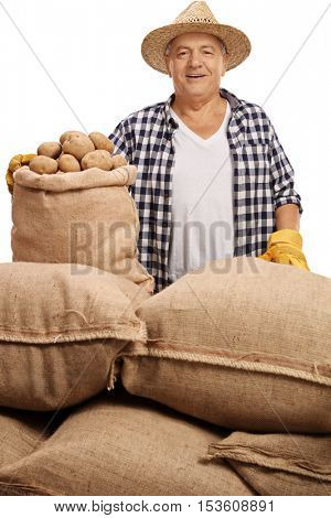 Mature agricultural worker posing with burlap sacks filled with potatoes isolated on white background