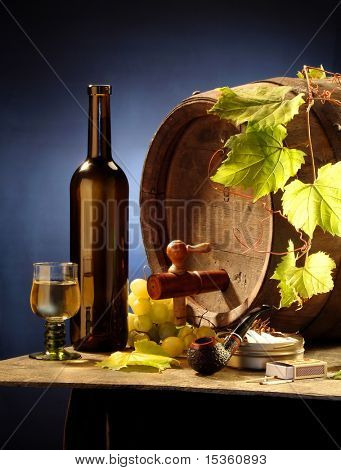 Still-life with white wine, a cask, a grapevine and a pipe on blue background