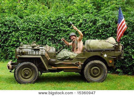 Man in military style in old fighting american jeep Willys