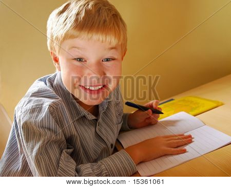 Smiling cute boy doing his homework