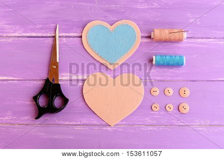 How to create a felt heart crafts. Step. Join blue and beige felt pieces using beige thread. Scissors, thread, buttons, needle on wooden background. Present for Valentine's day, wedding, mother's day
