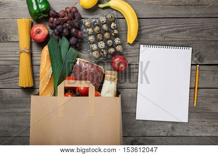 Groceries in paper bag on wooden table with blank album for your text top view