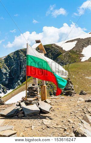 Bulgarian flag at the peak near Seven Rila Lakes in National Park Rila, Bulgaria