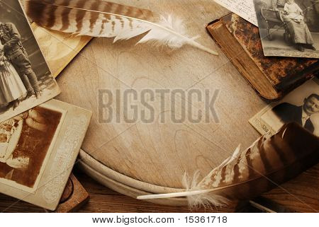 Vintage background with old photographs and feathers